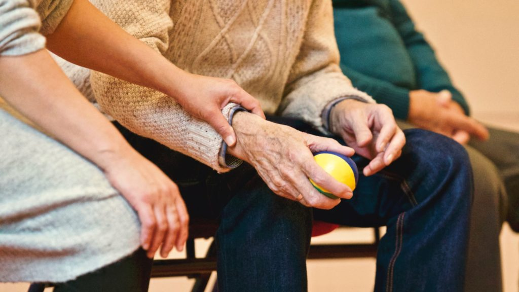 Eldery hand being held in hospice care on Cool Running Rental's blog post