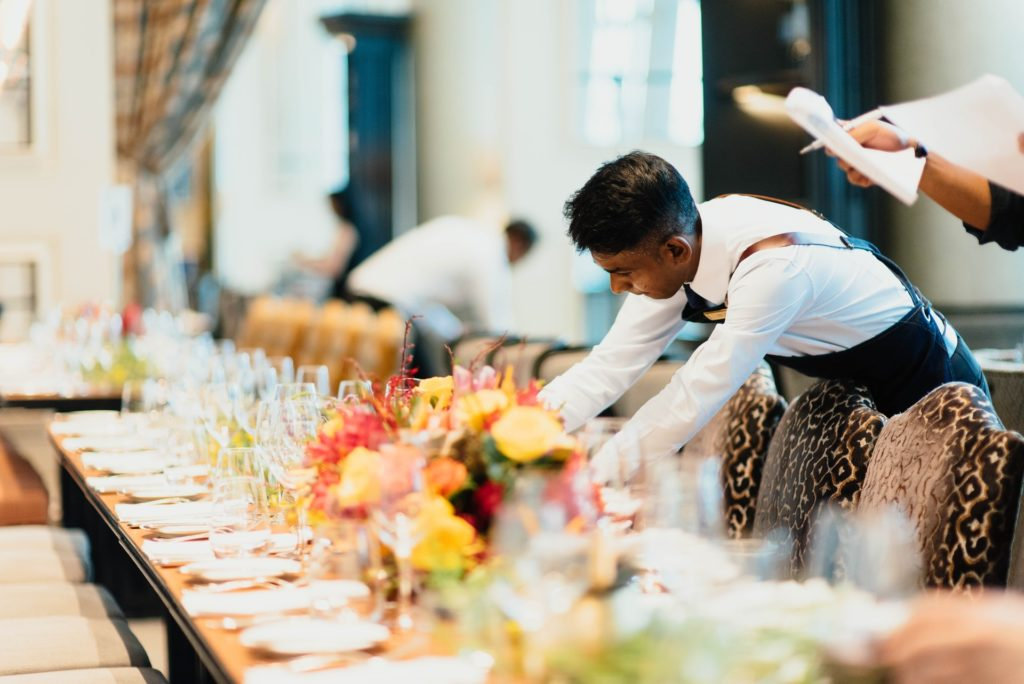 a waiter setting a table before an event