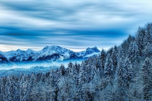 a winter landscape photo of snowy mountains and forests