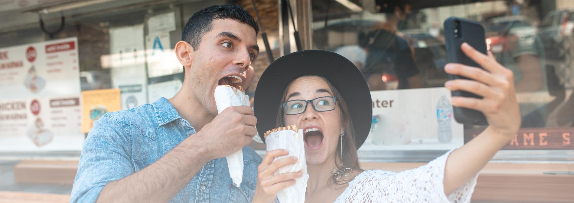 man and woman eating mobile street food
